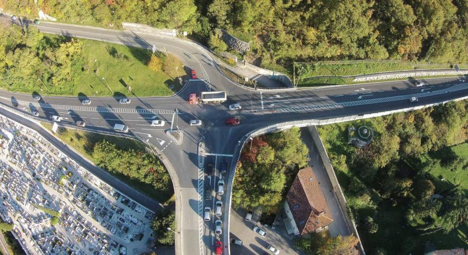 Zračni posnetek križišča, kjer se na glavno cesto G2-103 priključujeta cesti R2-402 in R3-608. Cesta G2-103 predstavlja glavno prometno povezavo Zgornje Soške doline z Novo Gorico. Cesta R2-402 povezuje Goriška Brda s Solkanom, cesta R3-608 povezuje Solkan (Novo Gorico), čez planoto Banjšice, s Čepovanom. Foto: DRSI