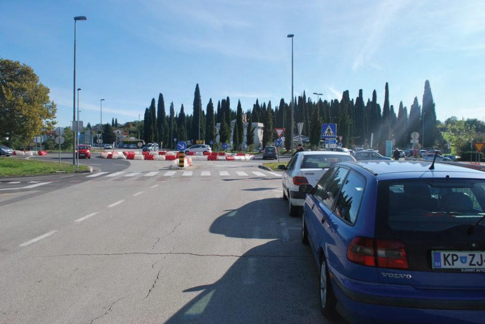 Parkirana vozila na lokalni cesti (zahodni krak), ki zmanjšujejo pogled na kolesarje in pešce. Foto: DRSI