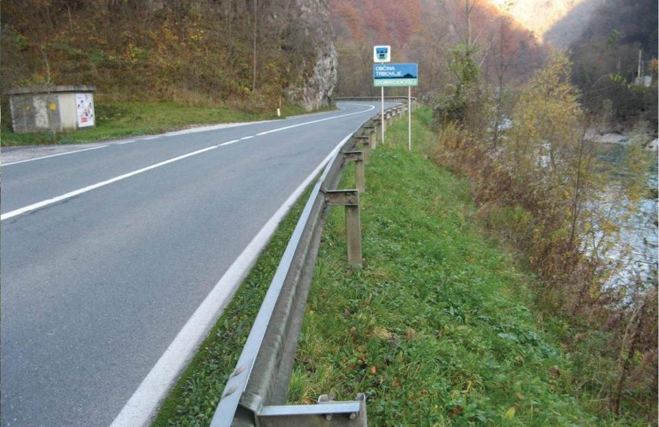 Pogled na potek ceste v smeri proti Trbovljam (v nasprotni smeri stacionaže), v ospredju nedefinirana makadamska površina in skalna brežina ter jeklena varnostna ograja. Foto: DRSI