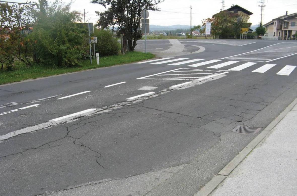 Pogled proti križišču. V ospredju poškodbe na vozišču in nedefinirana asfaltna površina. Foto: DRSI
